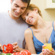 Cheerful young cooking couple at home - Foto Stock