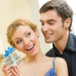 Cheerful amorous couple with gifts, indoors - Stock Photo