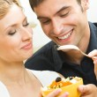 Cheerful young couple with vegetarian salad at home — Stock Photo #13189917