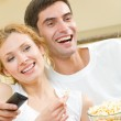 Cheerful young couple watching TV together — Stock Photo