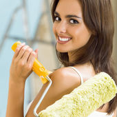 Woman with paint roller in new house — Stock Photo