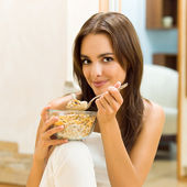 Young woman eating cereal muslin (flakes) — Foto de Stock