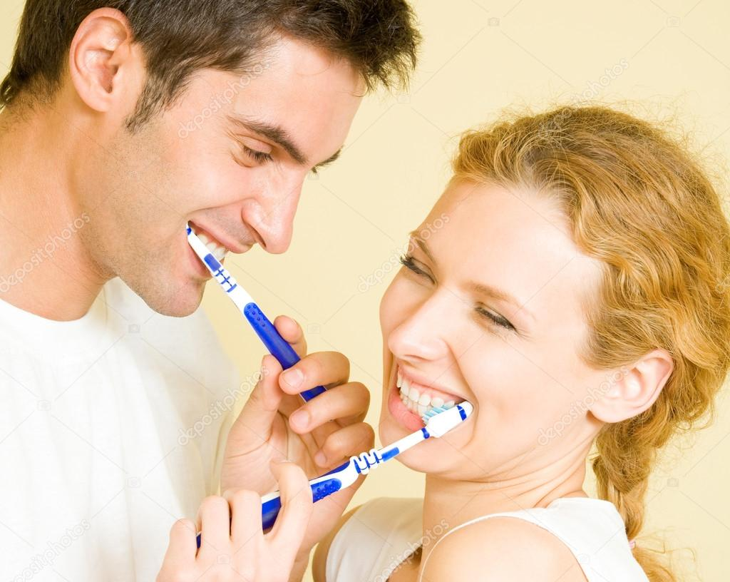 Cheerful young couple cleaning teeth together — Stock Photo #13190436