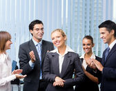 Cheerful businesswoman with apploading team — Stock Photo