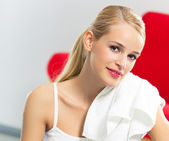 Cheerful woman in fitness wear with towel, at home — Stock Photo