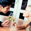 Couple with champagne at restaurant — Stock Photo #13597256