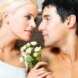 Cheerful couple with roses, indoor — Stock Photo