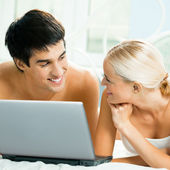 Cheerful couple with laptop, at home — Stock Photo