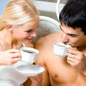 Casal alegre com copos de café, interior — Foto Stock