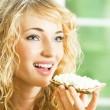 Portrait of young happy woman eating crispbread — Stock Photo