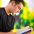 Young happy man reading book or textbook, outdoor — Foto Stock