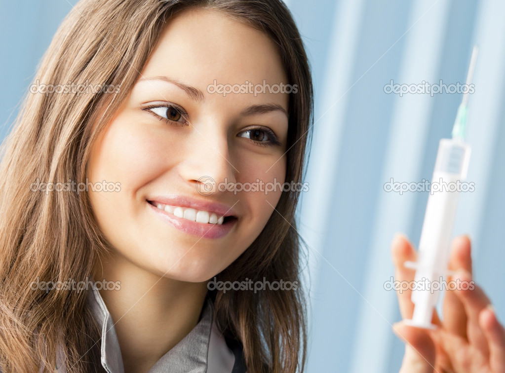 Happy smiling young female doctor with syringe at office  Stock Photo #13887708