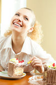 Cheerful blond young woman eating torte — Stock Photo