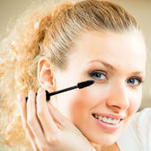 Cheerful woman applying mascara with lash brush — Stock Photo