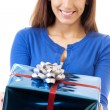 Cheerful woman showing gift, over white — Foto de Stock
