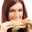 Stock Photo: Cheerful womeating sandwich with cheese