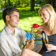 Young couple with gifts, rosa and champagne, outdoor — Stock Photo