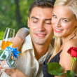 Young couple with gifts, rosa and champagne, outdoor — Stock Photo #14327309