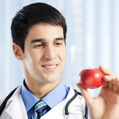 Smiling doctor with apple, at office — 图库照片