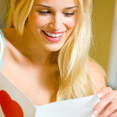 Happy blond woman with valentine card, at home — Stock Photo