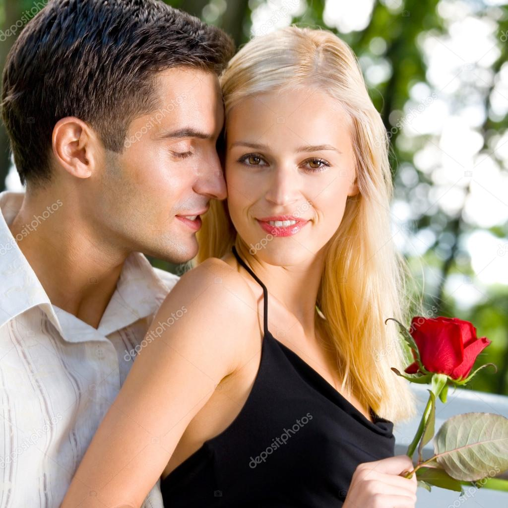Young happy amorous cheerful couple with rose, outdoor — Stock Photo #14327279