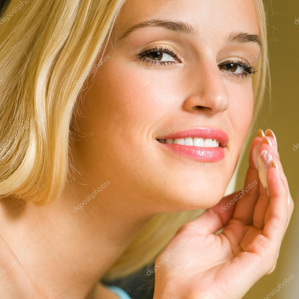 Portrait of young happy smiling cheerful beautiful blond woman applying creme, at home — Stock Photo #14327993