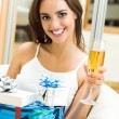 Cheerful woman with champagne and gifts — Stock Photo