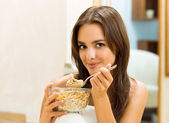 Young woman eating cereal muslin (flakes) — Stock Photo
