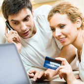 Cheerful couple paying by plastic card — Foto de Stock