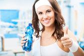 Donna con bottiglia d'acqua, al centro fitness — Foto Stock