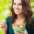 Young woman with salad, outdoors - Stock Photo