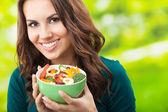 Mujer joven con ensalada, al aire libre — Foto de Stock
