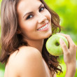 Young happy smiling woman with apple, outdoors — Stock Photo #16268623