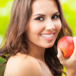 Young happy smiling woman with apple, outdoors — Stock Photo