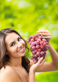 Young happy smiling woman with grapes, outdoors — Stock Photo