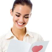 Joven mujer feliz lectura de tarjeta de san valentín, aislada — Foto de Stock