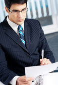 Portrait of reading businessman working at office — Stock Photo