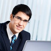 Smiling businessman working with laptop at office — Stock Photo
