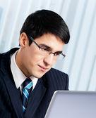 Sonriendo empresario trabaja con el portátil en oficina — Foto de Stock