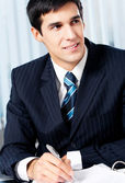 Successful businessman with documents at office — Stock Photo