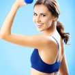 Woman in fitness wear with dumbbell, over blue — Stock Photo #18370223