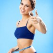 Woman in fitness wear with tape, over blue — Stock Photo #18370341