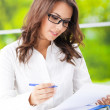 Young smiling businesswoman working at office — Stock Photo