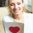 Cheerful smiling woman, reading valentine card — Stock Photo #18940619