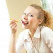 Cheerful blond young woman eating torte — Stock Photo #18941011