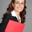 Businesswoman with folder, on gray — Stock Photo