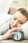 Woman with alarmclock on the bed — Stock Photo