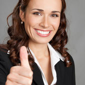 Businesswoman with thumbs up, over grey — Stock Photo