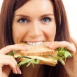 Cheerful woman eating sandwich with cheese — Stock Photo