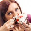 Cheerful woman eating pie, over white — Stock fotografie